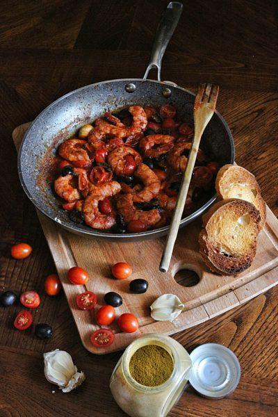 Gamberoni in padella al brandy -con curry, pomodoro e olive-